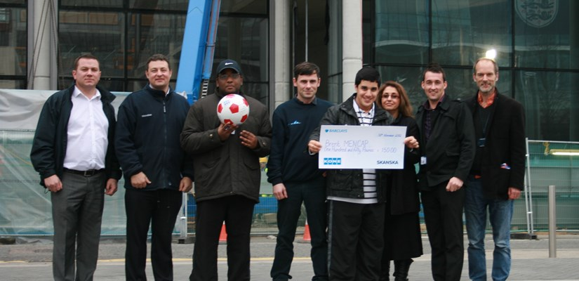 Nahil and Joel collect the cheque on behalf of Brent Mencap