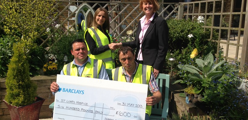 The team working on the new Woodlands School hands over the cheque to St Lukes Hospice
